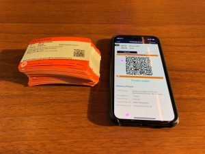 81 paper rail tickets alongside an iphone displaying a digital ticket alternative emblazoned on a smartphone; Rail Internet of Things and connected devices will make this digital alternative a widespread reality