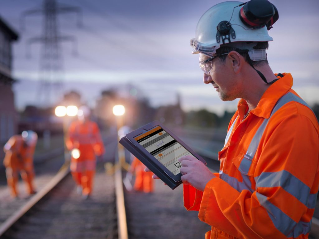 A rail worker wearing protective clothing using the ePIC app on a tablet whilst on a track side work site.